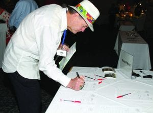 Tom James bidding on artwork at The Art in the Park event he hosted for Chi Chi Rodriguez Foundation