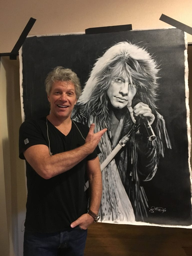 Jon Bon Jovi looks on the art of himself done by John Douglas